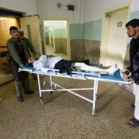 Men carry an injured man inside a hospital a day after a bomb blast and gunfire at a military hospital in Kabul Thursday. | REUTERS