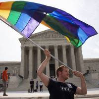 John Becker of Silver Spring, Maryland, waves a rainbow flag in support of gay marriage outside of the Supreme Court in Washington in 2015. LGBT advocates are questioning the Trump administration's quiet deletion of questions on sexuality from two federal surveys. | AP