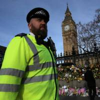 A policeman walks past floral tributes to the victims of the March 22 terror attack in front of the Elizabeth Tower, more commonly referred to as Big Ben in central London on Sunday. The British government said its security services must have access to encrypted messaging applications such as WhatsApp, revealing it was used by the killer behind the Parliament attack. | AFP-JIJI