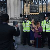 People pose for a picture with police officers outside the Houses of Parliament in central London on Sunday. | AFP-JIJI
