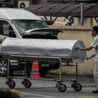 Hospital workers move a body cart to the gate of the forensics wing of the Hospital Kuala Lumpur, where the body of Kim Jong Nam is being held, in Kuala Lumpur on March 21. Kim, the half-brother of North Korean leader Kim Jong Un, was assassinated in Malaysia on Feb. 14. | AFP-JIJI