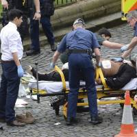 Khalid Masood is treated by emergency services outside the Houses of Parliament in London on Wednesday. | AP