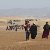 Displaced Iraqis flee their homes as Iraqi forces battle with Islamic State militants, in village of Badush northwest of Mosul, Iraq, Saturday. | REUTERS