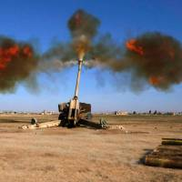 Iraqi fighters from the Abbas Brigade, which fights under the umbrella of the Shiite popular mobiliation units, fire toward enemy positions in village of Badush, some 15 km northwest of Mosul, during the ongoing battle to retake the city's west from Islamic State (IS) group jihadis on Thursday. | AFP-JIJI