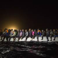 Refugees and migrants from many different African nationalities sit aboard an overcrowded rubber boat leaving Libyan territorial waters early Sunday. The Spanish NGO Proactiva Open Arms found the boat after a long search coordinated with Italian authorities and took everyone aboard its ship.   AP