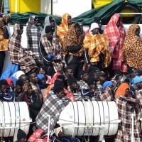 Would-be immigrants wait to disembark in the port of Catania, Sicily, on March 21 from the ship Aquarius' following a rescue operation in the Mediterranean. The Aquarius, a humanitarian ship run by the NGO SOS Mediterranean and Doctors Without Borders (MSF), said it saved 946 people, including 200 unaccompanied minors rescued after being found drifting on nine wooden and rubber boats. | AFP-JIJI