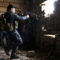 A sniper of the Iraqi Federal Police takes his position at a destroyed builiding near Islamic State positions at Bab al Jadid district in the Old City of Mosul, Iraq, Monday. | REUTERS