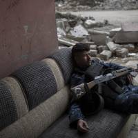 A Federal Police soldier rests before moving to a front line near the old city during fighting against Islamic State militants on the western side of Mosul, Iraq, Tuesday. | AP