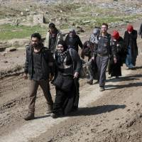 Iraqi civilians flee their homes due to fighting between Iraqi security forces and Islamic State militants, on the western side of Mosul, Iraq, Sunday. | AP
