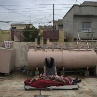 A man prepares the body of Suheyil Najn Abdullah to be buried after he was killed by a sniper trying to flee fighting between Iraqi security forces and Islamic State on the western side of Mosul, Iraq, Thursday. | AP
