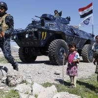 Displaced Iraqi children, who fled their homes in the Old City in western Mosul due to the ongoing fighting between government forces and Islamic State (IS) group fighters, are seen looking toward a security forces member ahead of being taken to the Hammam al-Alil camp, south of Mosul, on Monday. | AFP-JIJI