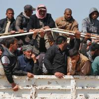 Displaced Iraqis, who fled their homes in the Old City in western Mosul due to the ongoing fighting between government forces and Islamic State (IS) group fighters, are taken to the Hammam al-Alil camp, south of Mosul Monday. | AFP-JIJI