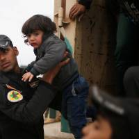 An Iraqi soldier helps a displaced child out of a truck as Iraqi forces battle with Islamic State militants, in western Mosul, Iraq, Tuesday. | REUTERS