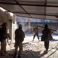 A still image taken from a video posted to a social media website by the Islamic State-affiliated Aamaq News Agency on Sunday shows men, said to be Islamic State fighters, firing their weapons, said to be in western Mosul, Iraq. | SOCIAL MEDIA WEBSITE / VIA REUTERS TV