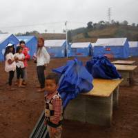 Refugees who fled fighting in neighboring Myanmar stand in a Chinese disaster relief tent camp in the town of Nansan, Yunnan province, China, March 12. | REUTERS