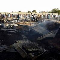 Residents of the Muna camp gather near the site of an explosion on March 22. At least four suicide bomb blasts rocked a camp for migrants fleeing Boko Haram insurgents in restive northeastern Nigeria, killing at least three people and wounding 20, officials said. | AFP-JIJI