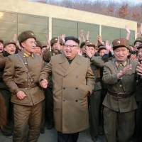 North Korean leader Kim Jong Un is applauded after watching the test of a high-thrust rocket engine on Saturday. | REUTERS