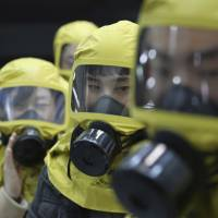 South Korean government officials wearing gas masks attend a civil defense drill against a possible North Korean chemical weapons attack at their office in Seoul on Wednesday. | AP