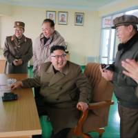 North Korean leader Kim Jong Un smiles after the test of a new high-powered engine in this undated picture released Sunday.   REUTERS