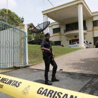A Malaysian police officer cordons off the North Korean Embassy in Kuala Lumpur on Tuesday amid a bitter diplomatic dispute between the two countries over the poisoning death of leader Kim Jong Un's estranged half brother.   AP