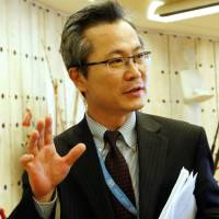 Mun Jong Chol, a counselor at the North Korea mission to the U.N. in Geneva, talks with journalists outside a meeting of the U.N.'s Human Rights Council on Friday. | REUTERS