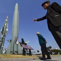 Visitors look at replicas of a North Korean Scud-B missile (center) and a South Korean Nike missile (left) at the Korean War Memorial in Seoul on March 22. | AFP-JIJI