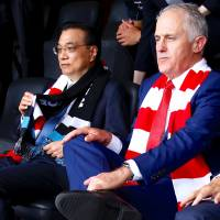 Australian Prime Minister Malcolm Turnbull sits with Chinese Premier Li Keqiang as they watch an Australian Football League game at the Sydney Cricket Ground in the Australian capital on Saturday. | REUTERS