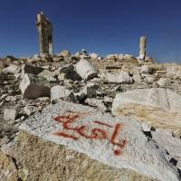 Graffiti sprayed by Islamic State militants reads, 'We remain' on a stone at the Temple of Bel in the historic Syrian city of Palmyra on April 1, 2016. | REUTERS