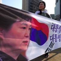 Supporters of South Korea's impeached President Park Geun-Hye hold a banner showing a portrait of Park during a rally demanding a repeal of the impeachment in Seoul on Saturday. | AFP-JIJI