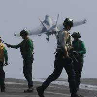 A U.S. Navy F-18 fighter jet from the aircraft carrier USS Carl Vinson takes off for a patrol in the disputed South China Sea on Friday. | AP