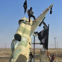 Islamic State fighters wave the group's flag from a damaged government fighter jet following the battle for the Tabqa air base, in Raqqa, Syria, in this undated photo posted to the internet in August 2014. | AP