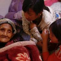 Refugees who fled fighting in neighboring Myanmar talk Saturday to a 96-year-old family member in the house of a relative in the village of Baiyan, near Nansan in Yunnan province, China. | REUTERS