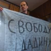 Russian opposition activist Ildar Dadin, 34, displays a banner reading 'Freedom for Dadin' during a media interview in Moscow on March 3. | AFP-JIJI