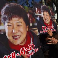 Pro-government activists hold portraits of South Korean President Park Geun-hye outside the Constitutional Court in Seoul on Feb. 27 as the court held its final hearing in Park's impeachment trial. | AFP-JIJI