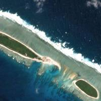 A combination of satellite photos shows Chinese-controlled North Island, part of the Paracel group in the South China Sea, on Feb. 15 (top) and on March 6. | REUTERS