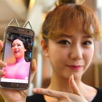 SixBomb member Hong Hye-jin (Soa) shows a photo of herself before her plastic surgery in Seoul on Thursday. | AFP-JIJI