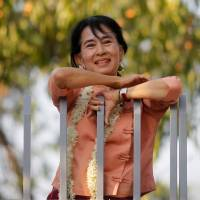 Myanmar's Aung San Suu Kyi smiles at supporters as she celebrates Thingyan, the water festival for the country's new year, in front of her home in Yangon in April 2012. | REUTERS