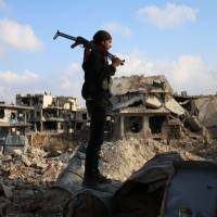 A rebel fighter stands amid the rubble of destroyed buildings in the rebel-held Syrian city of Daraa on March 14. | AFP-JIJI