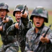 Chinese People's Liberation Army soldiers hold a drill during a media tour at a PLA engineering school in Beijing in July 2014. | REUTERS