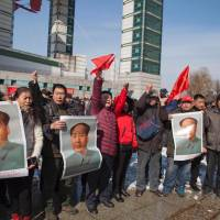 Residents hold posters showing late Communist Party leader Mao Zedong during a protest in Jilin, China, on Sunday calling for a boycott of South Korean goods due to the planned deployment in that nation of a U.S. missile-defense system. | AFP-JIJI