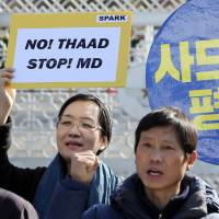 Protesters rally against deploying the Terminal High-Altitude Area Defense system outside the Defense Ministry in Seoul on Tuesday. | AP