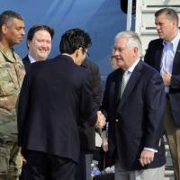 U.S. Secretary of State Rex Tillerson (second from right) is greeted by U.S. officials on Friday upon his arrival at Osan air base in Pyeongtaek, South Korea. | AP