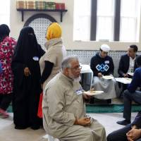 People attend an open house at the Darul Qur'an Mosque Saturday in Chicago. The open house was scheduled for neighbors to get acquainted with the Muslim culture and religion. U.S. President Donald Trump's efforts to institute a ban on travelers from certain Muslim-majority countries have been met with a strong response from Muslim-Americans and their supporters. | AFP-JIJI