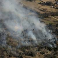Crews battling massive, deadly Plains wildfires hope to catch break as winds abate