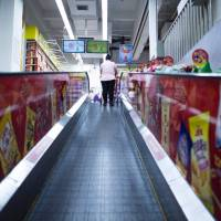 A Lotte Mart employee stands in an almost empty store in Shanghai on March 13. The Korean store was open but dozens of other Lotte stores in China have been closed amid a diplomatic row sparked by the deployment of a controversial U.S. missile system in South Korea hat has sparked Chinese boycott calls against Seoul.   AFP-JIJI