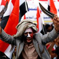 A man waves traditional daggers, or jambiyas, during a mass rally by supporters of the Houthi movement and former Yemeni President Ali Abdullah Saleh in Sanaa on Sunday. | REUTERS