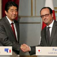 French President Francois Hollande (right) and Japan's prime minister, Shinzo Abe, signal their agreement after a press conference at the Elysee Palace in Paris Monday. | AP