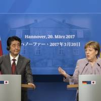 German Chancellor Angela Merkel and the prime minister of Japan, Shinzo Abe, address the media during a joint press conference as part of a meeting in Hanover, Germany, Monday. | PETER STEFFEN / DPA / VIA AP