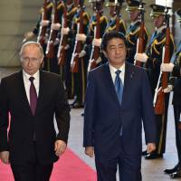 Prime Minister Shinzo Abe and Russian President Vladimir Putin walk past honor guards as they arrive at Abe's official residence in Tokyo on Dec. 16. Abe is reportedly visiting Russia later next month for talks with Putin. | VIA BLOOMBERG