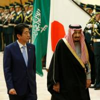 Prime Minister Shinzo Abe and Saudi King Salman bin Abdul-Aziz al-Saud review an honor guard in Tokyo before holding a meeting at Abe's office Monday. | REUTERS